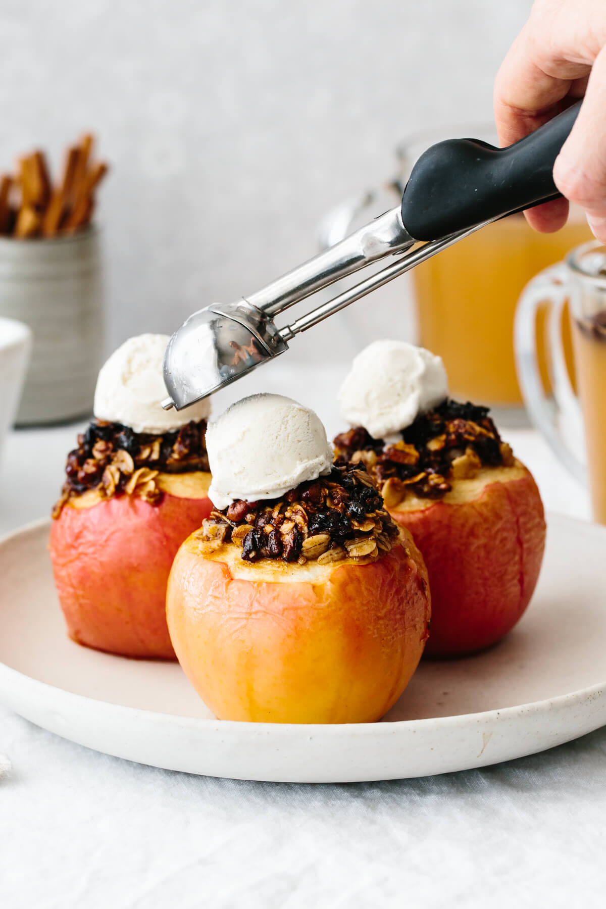 Topping the baked apples with a scoop of ice cream.