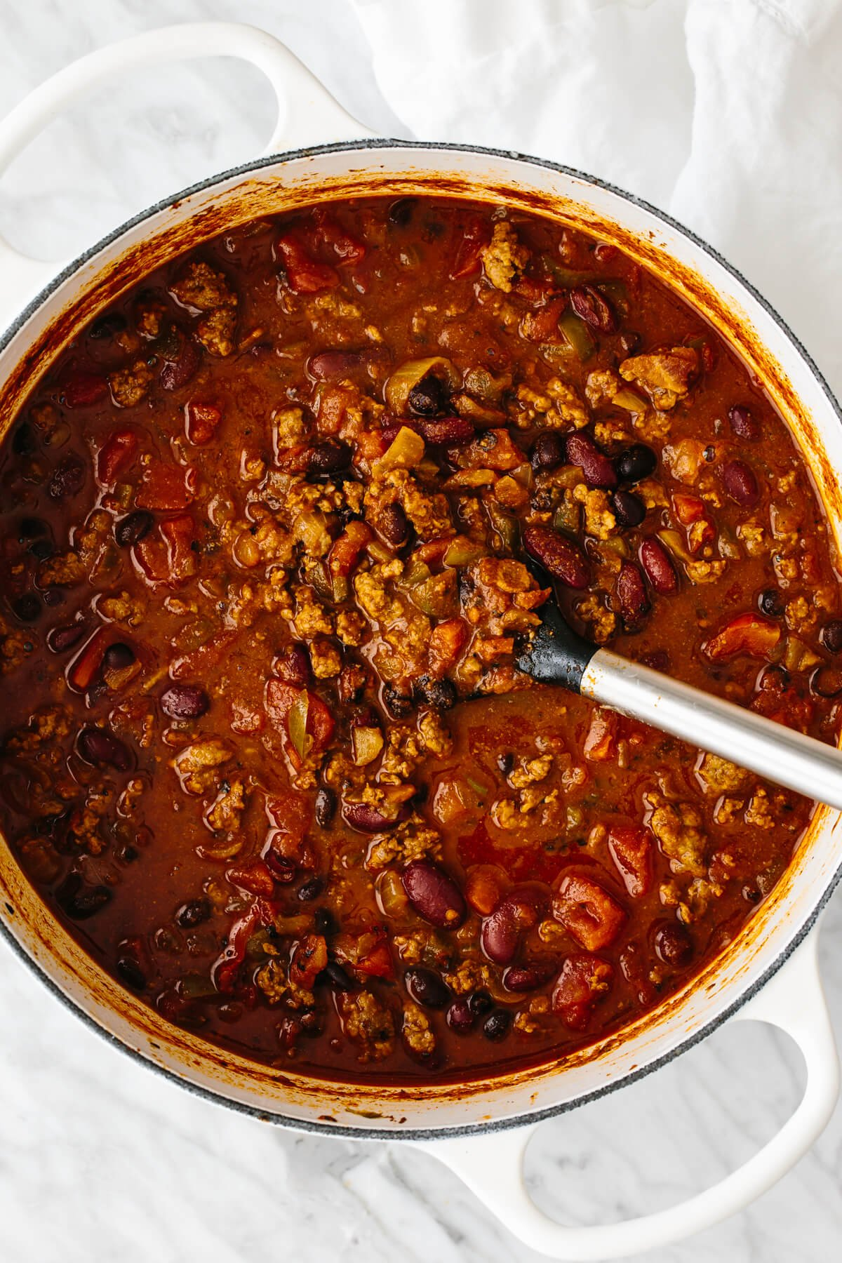 A big pot of chili with a large serving spoon in it.