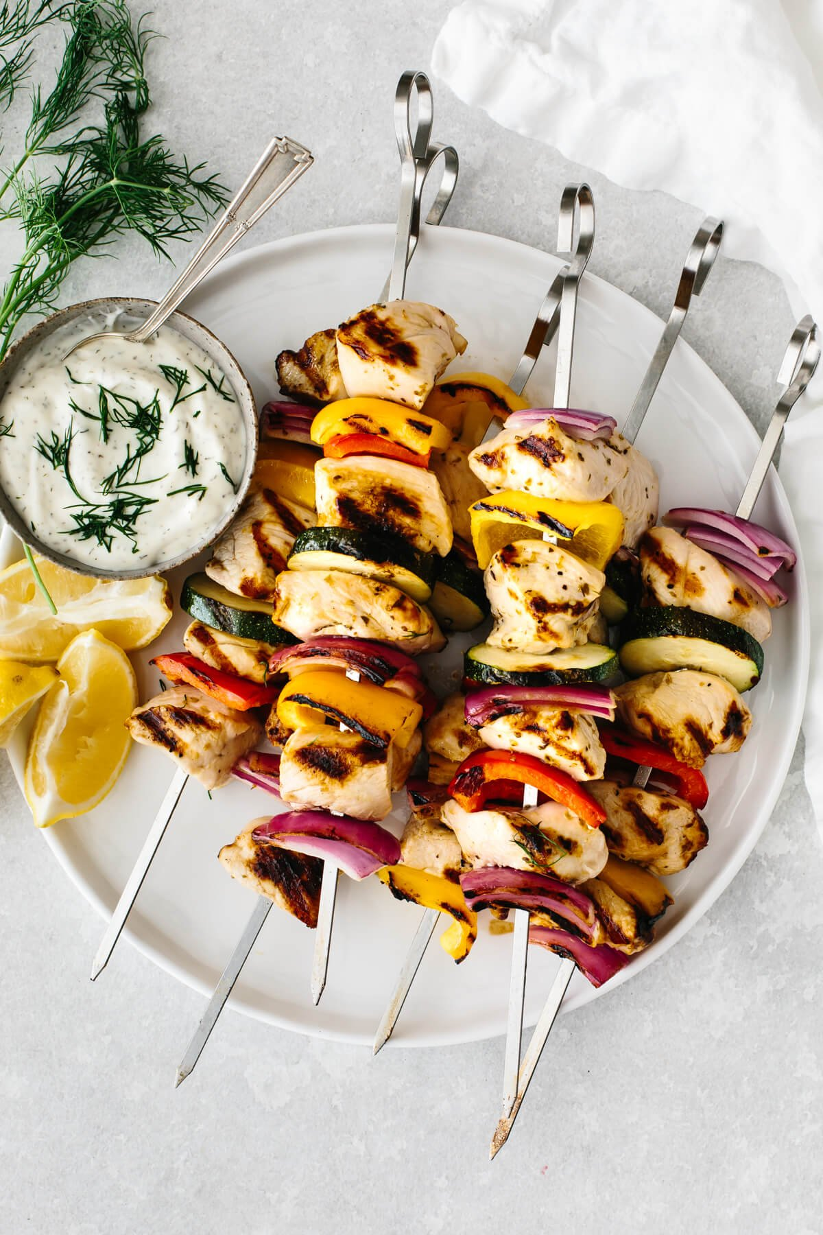 A plate full of cooked chicken kebabs, next to tzatziki sauce.