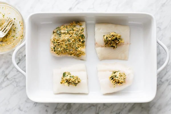 Garlic butter being spread on top of cod filets.