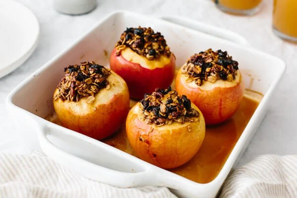 Four baked apples in a baking dish.