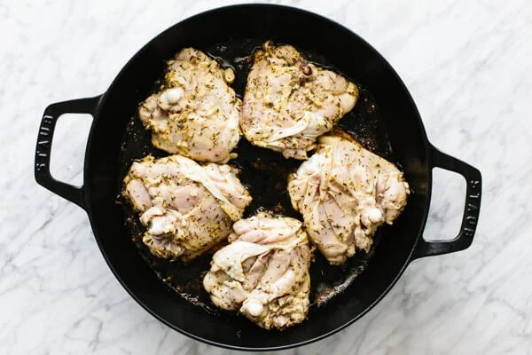 Searing the chicken skin side down in a pan.