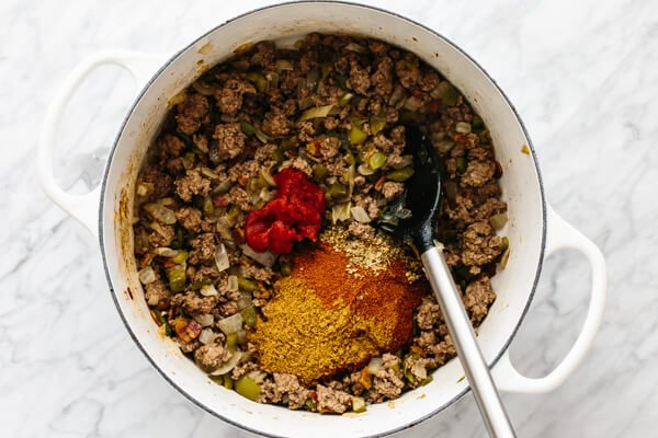 Sauteed beef, spices, and tomato paste in a pot.
