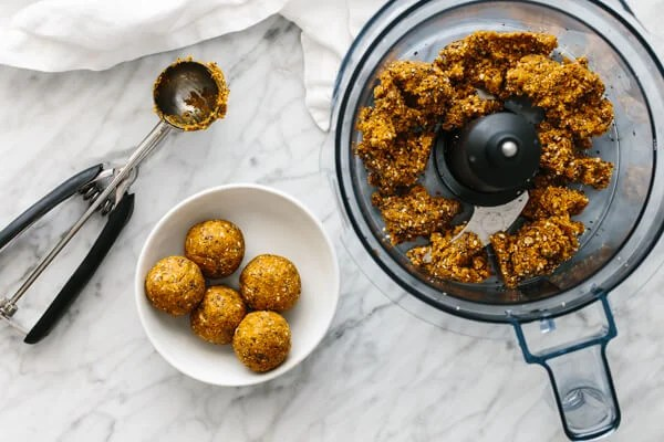 Blended mango energy balls in a food processor next to a bowl of them.