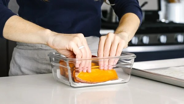 Placing cooked sweet potato toast into a storage container.