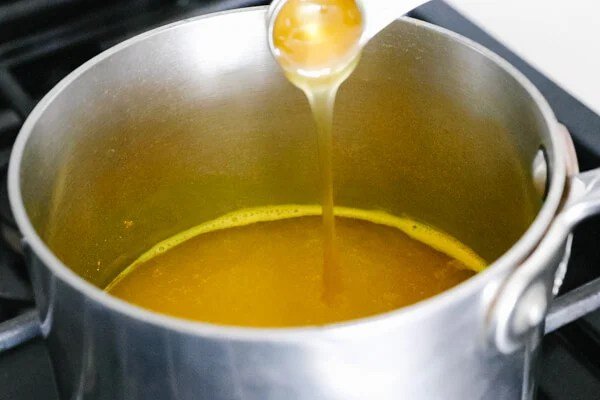 Pouring honey into the pot with turmeric tea.