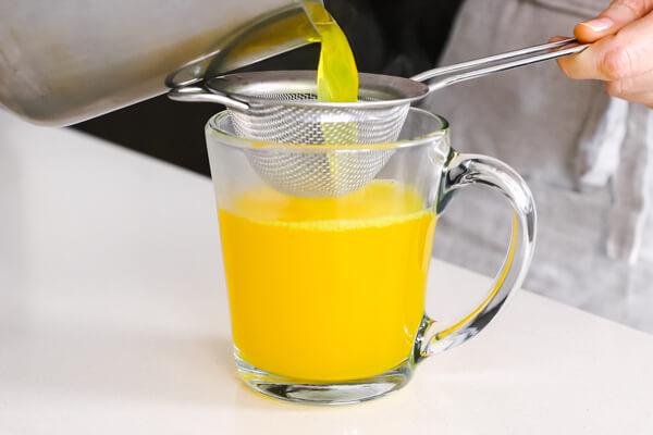 Straining the turmeric tea into a glass.