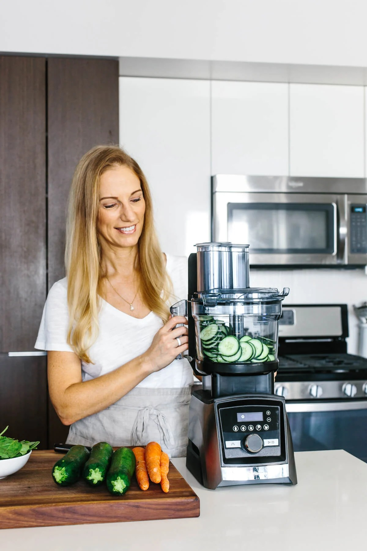 Girl looking at Vitamix food processor with sliced cucumber inside.