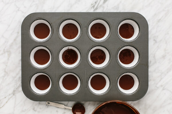Melted chocolate in muffin tin for almond butter cups.
