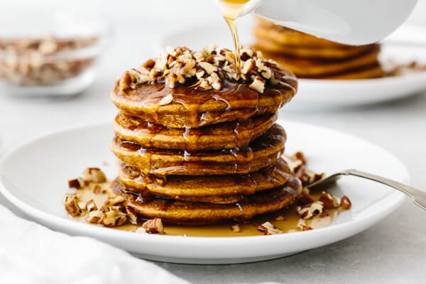 A stack of paleo pumpkin pancakes on a white plate, topped with pecans.