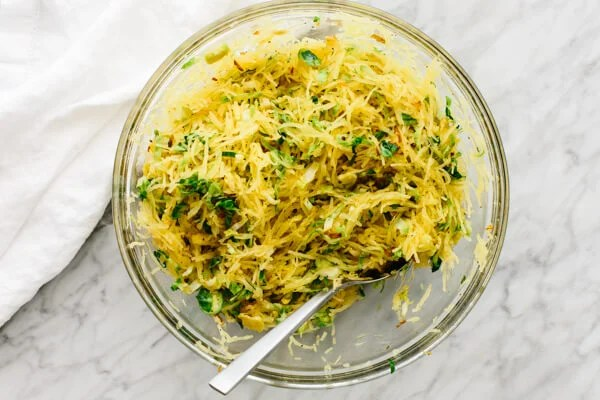 Spaghetti Squash, Brussels sprouts, and crispy shallots being mixed in a bowl.