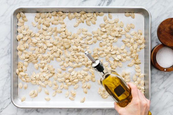 Drizzling oil for roasted pumpkin seeds on a baking sheet.