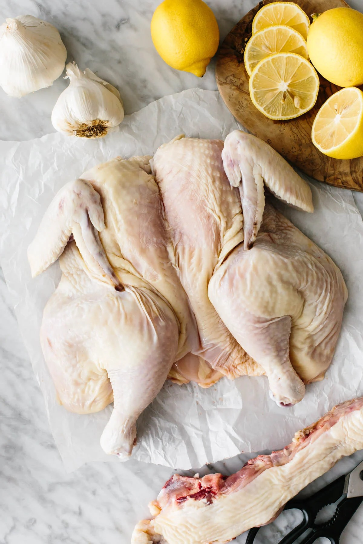 A spatchcocked chicken on a table with lemons.
