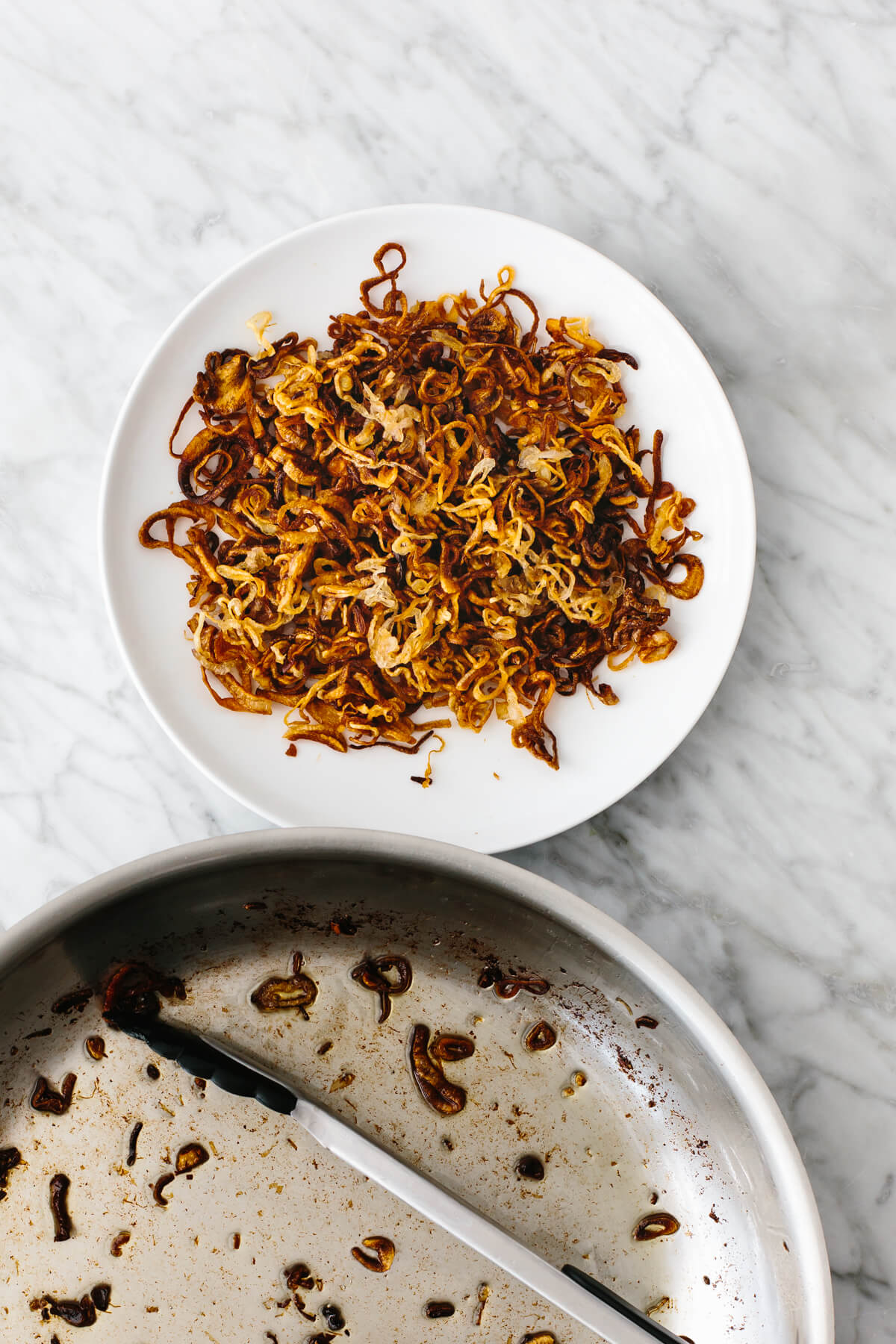 A pan next to a plate of crispy shallots