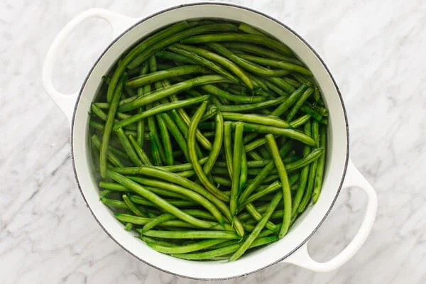 Beans being boiled in a pot for a healthy green bean casserole.