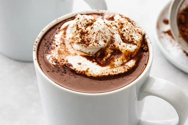 A whit mug with hot chocolate and whipped cream.