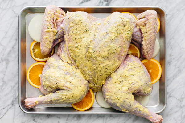 Spatchcock turkey on a baking sheet pan.