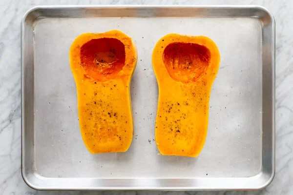 Butternut squash halves on a baking sheet for orange shakshuka.