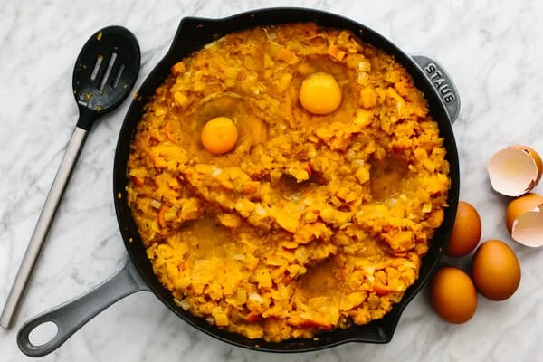 Adding eggs to an orange shakshuka in a skillet.