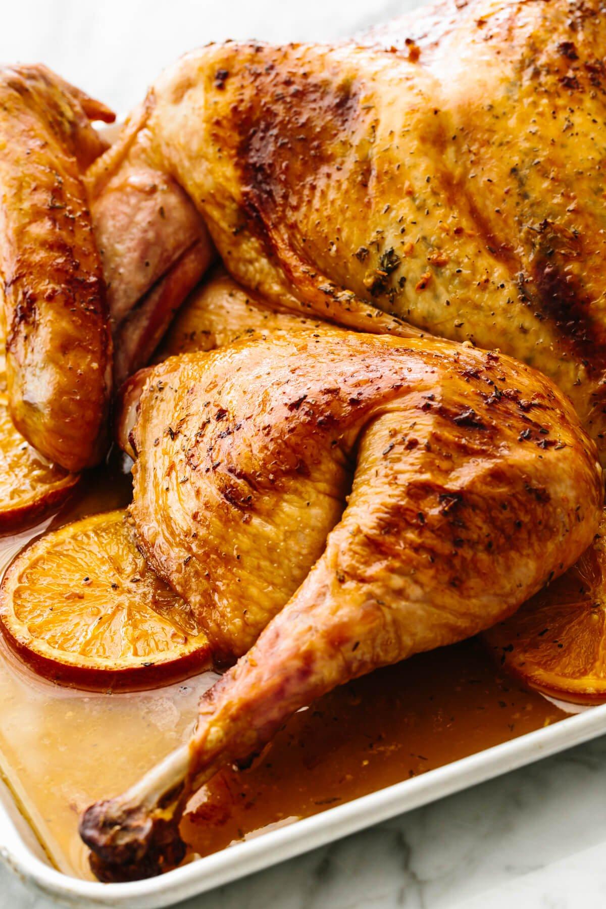 Maple orange glazed spatchcock turkey on a sheet pan.