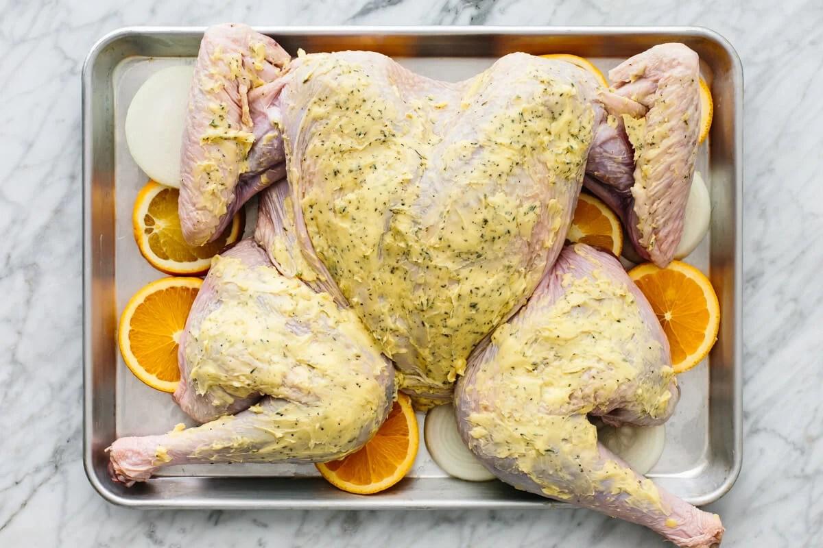 Maple orange glazed spatchcock turkey on a sheet pan before baking.