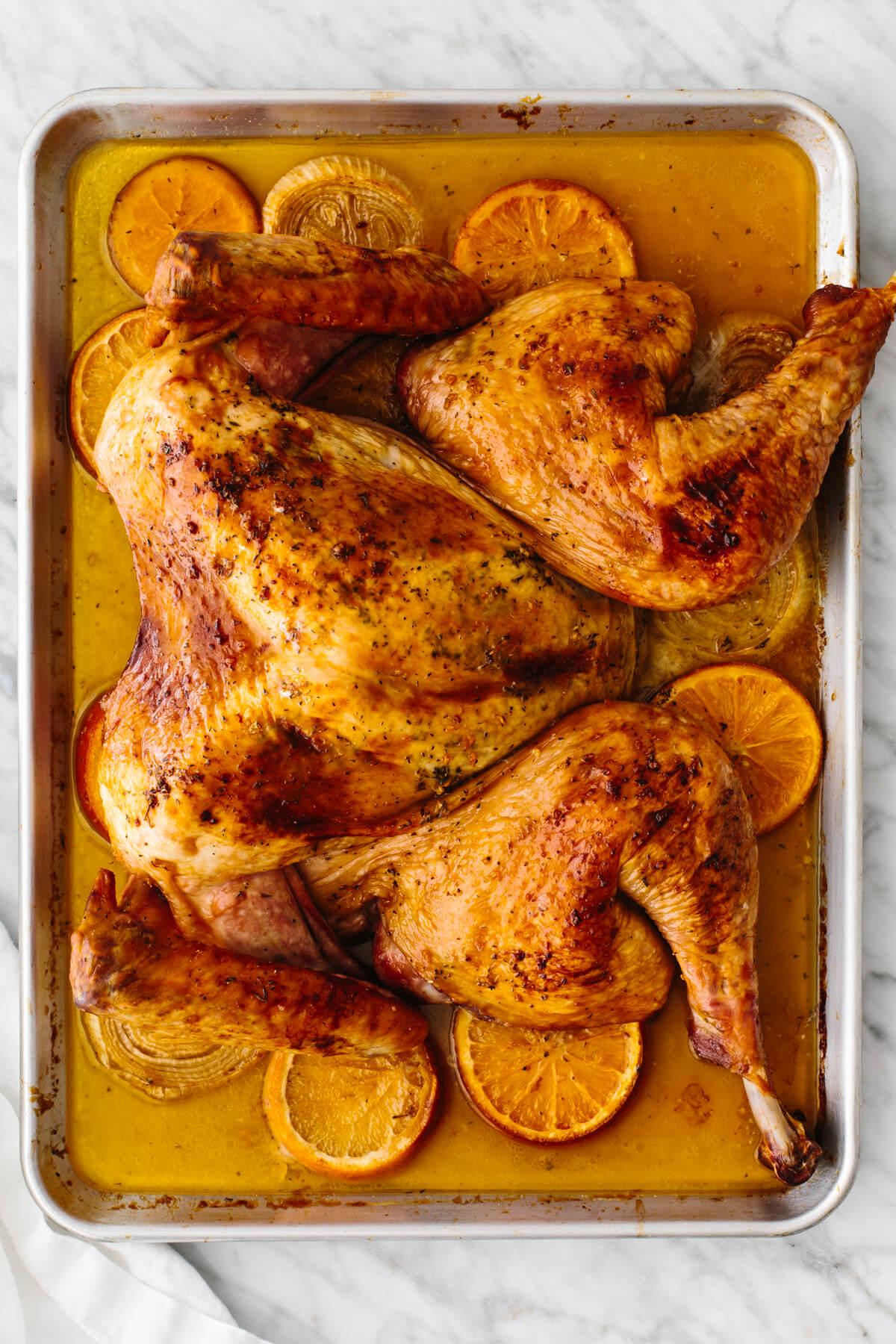 A baking sheet with an orange glazed spatchcock turkey