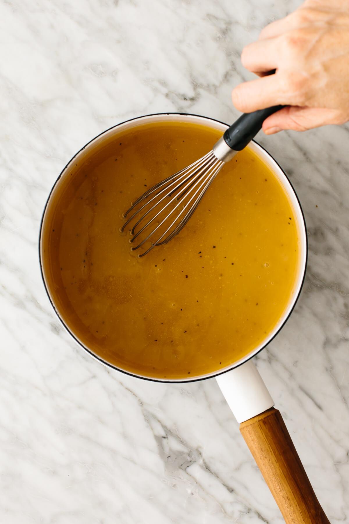 Whisking turkey gravy in a pot.