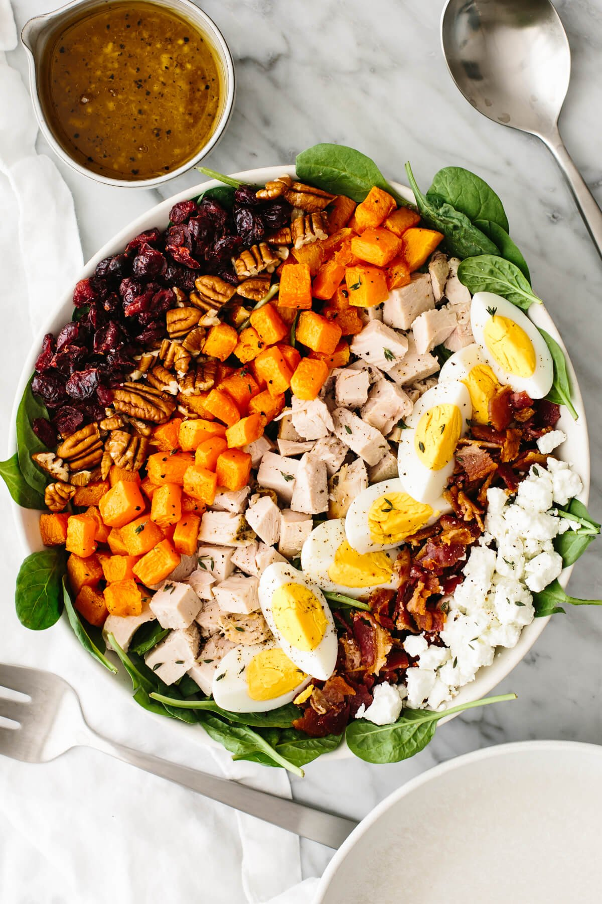 Turkey cobb salad in a large bowl on a table next to a spoon.
