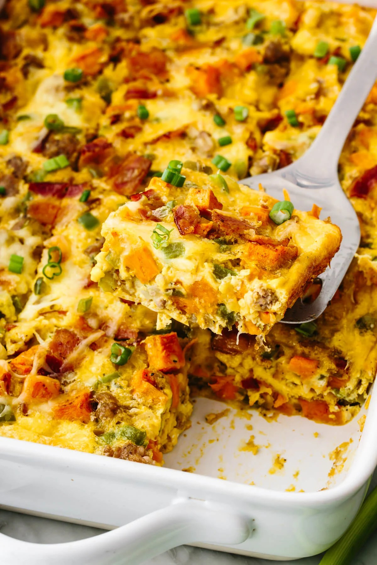 Scooping up a piece of a loaded breakfast casserole with a spatula.