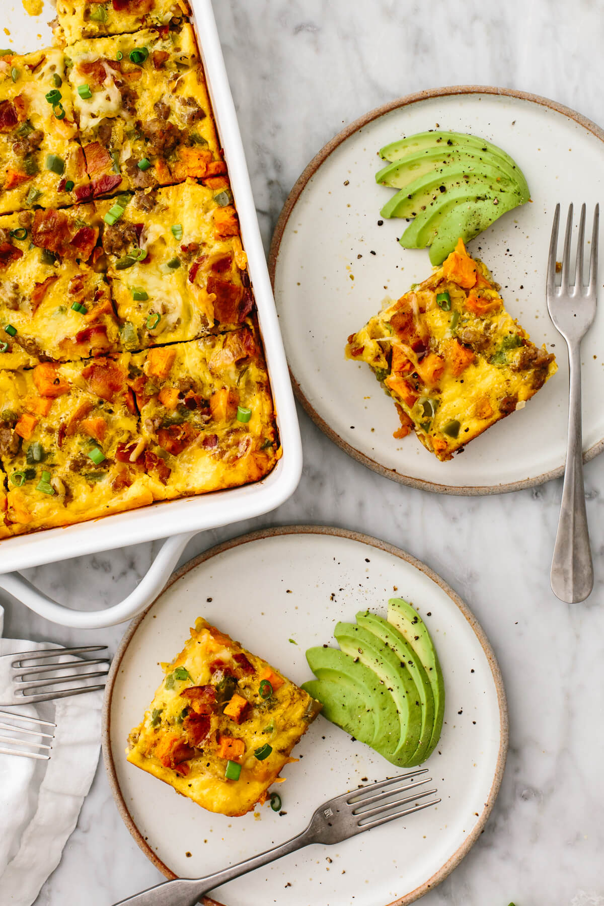 Loaded breakfast casserole pieces on two plates with avocado slices.
