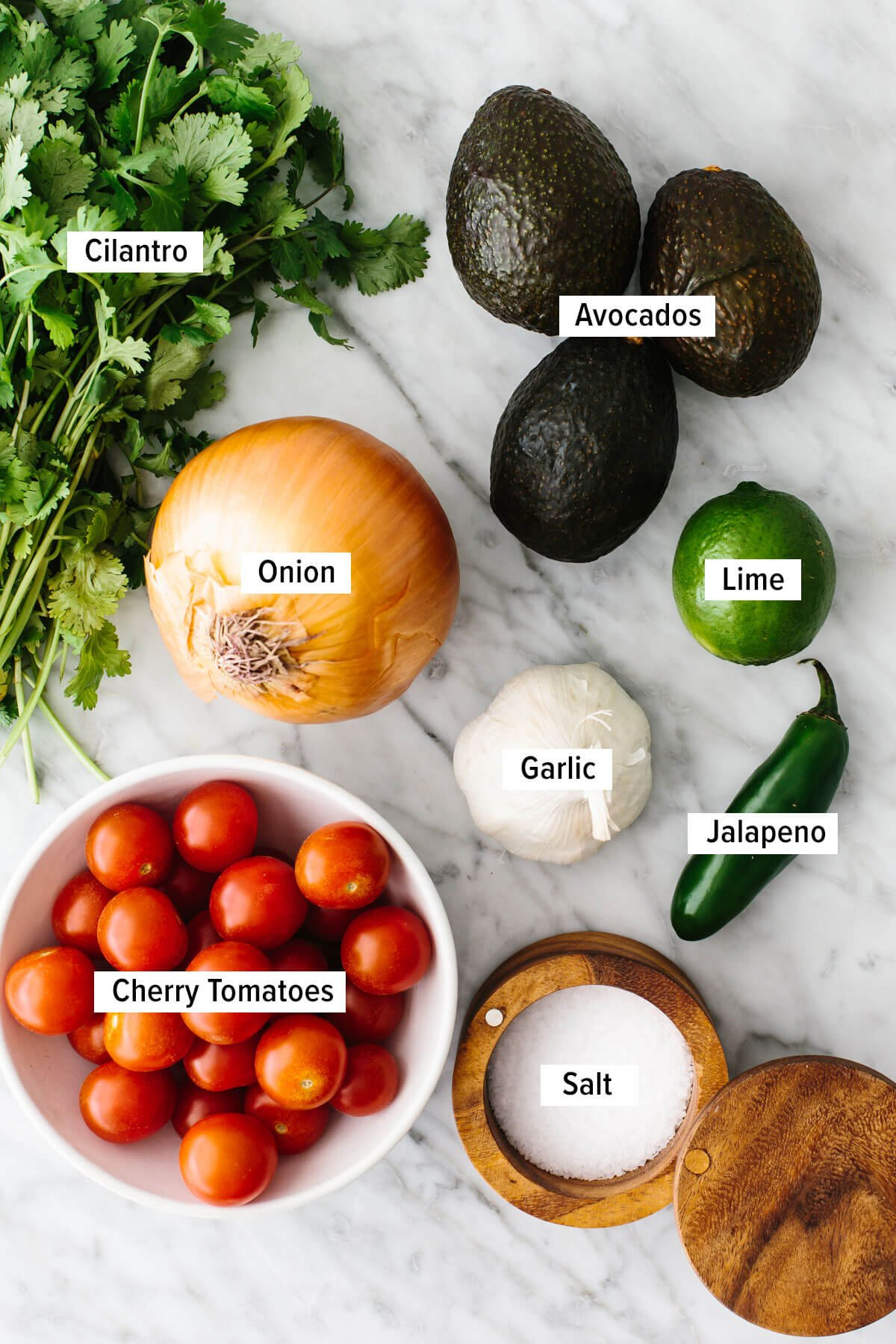 Ingredients for guacamole stuffed tomatoes on a table.