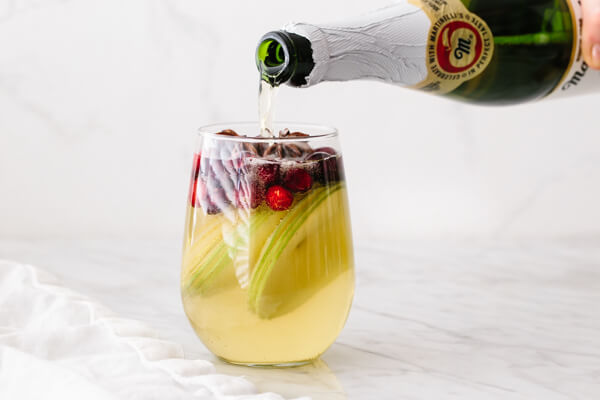 Pouring apple cider into a glass of white Christmas sangria.