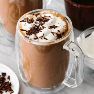 A glass of Nutella hot chocolate next to whipped cream.