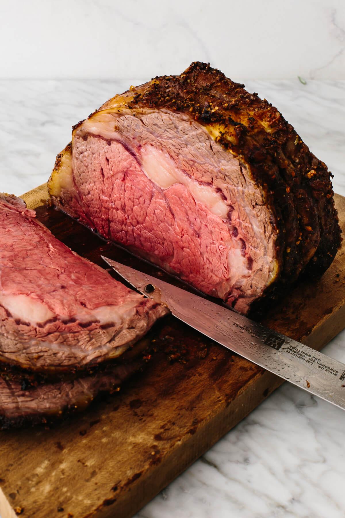 Prime rib on cutting board sliced up.