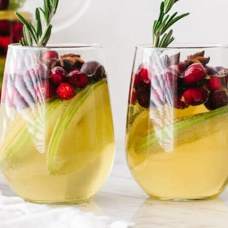 White Christmas sangria in two glasses on a table next to a pitcher.