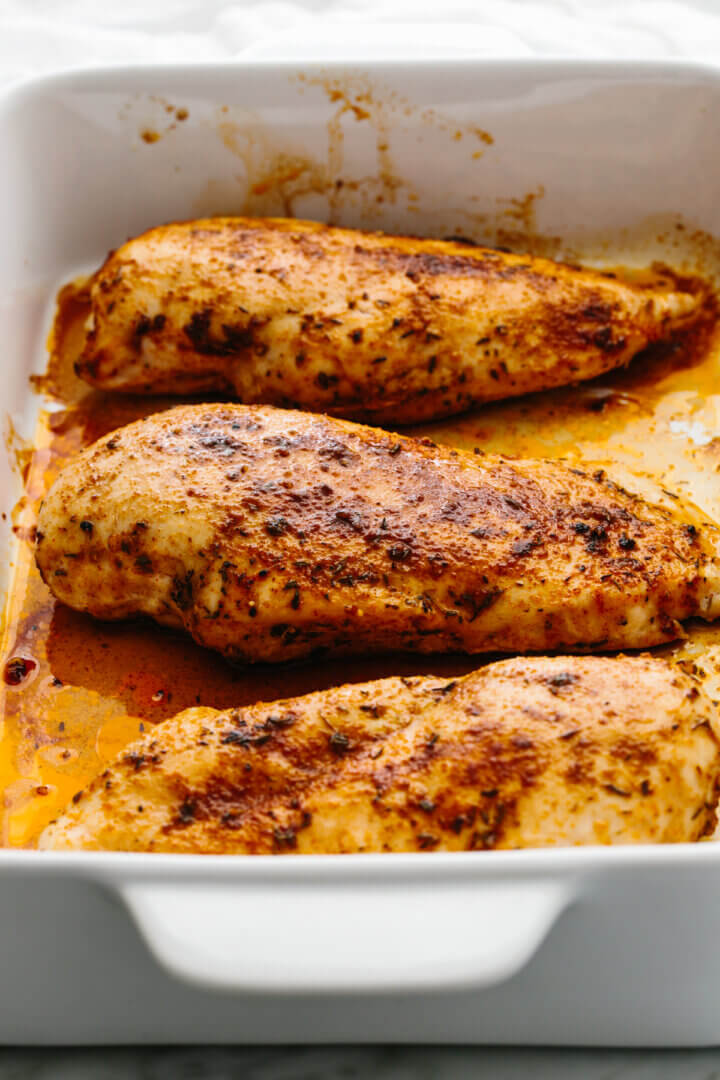 Baked chicken breasts in a pan.
