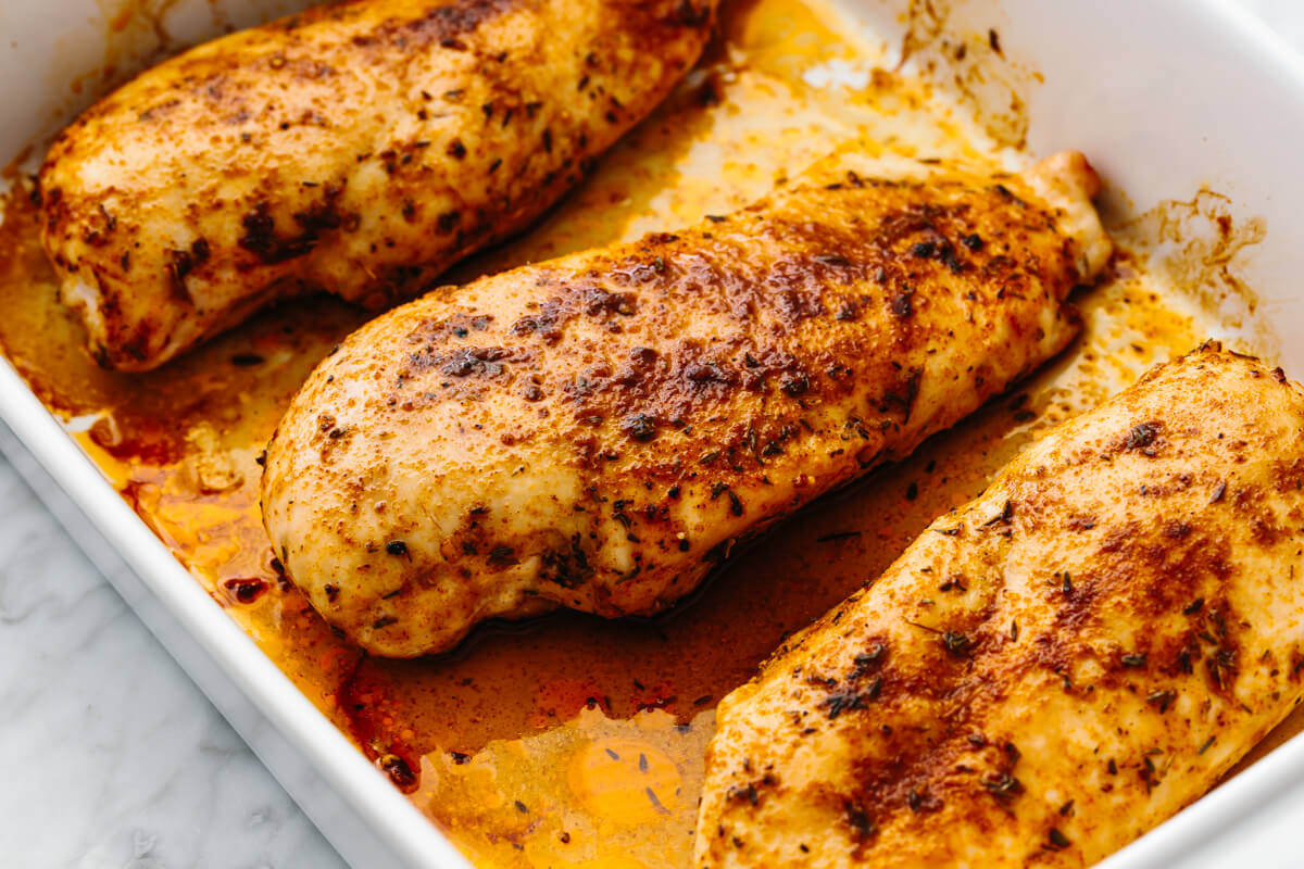 Baked chicken breasts in a pan on a table.