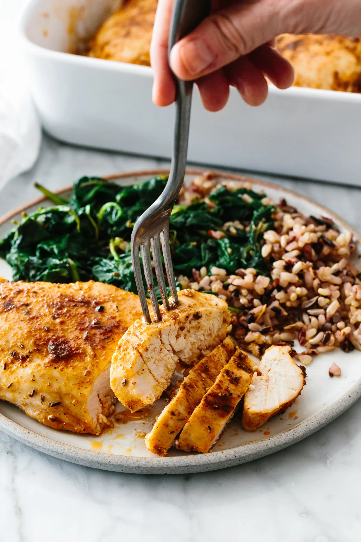 Baked chicken breast with spinach and rice on a plate.