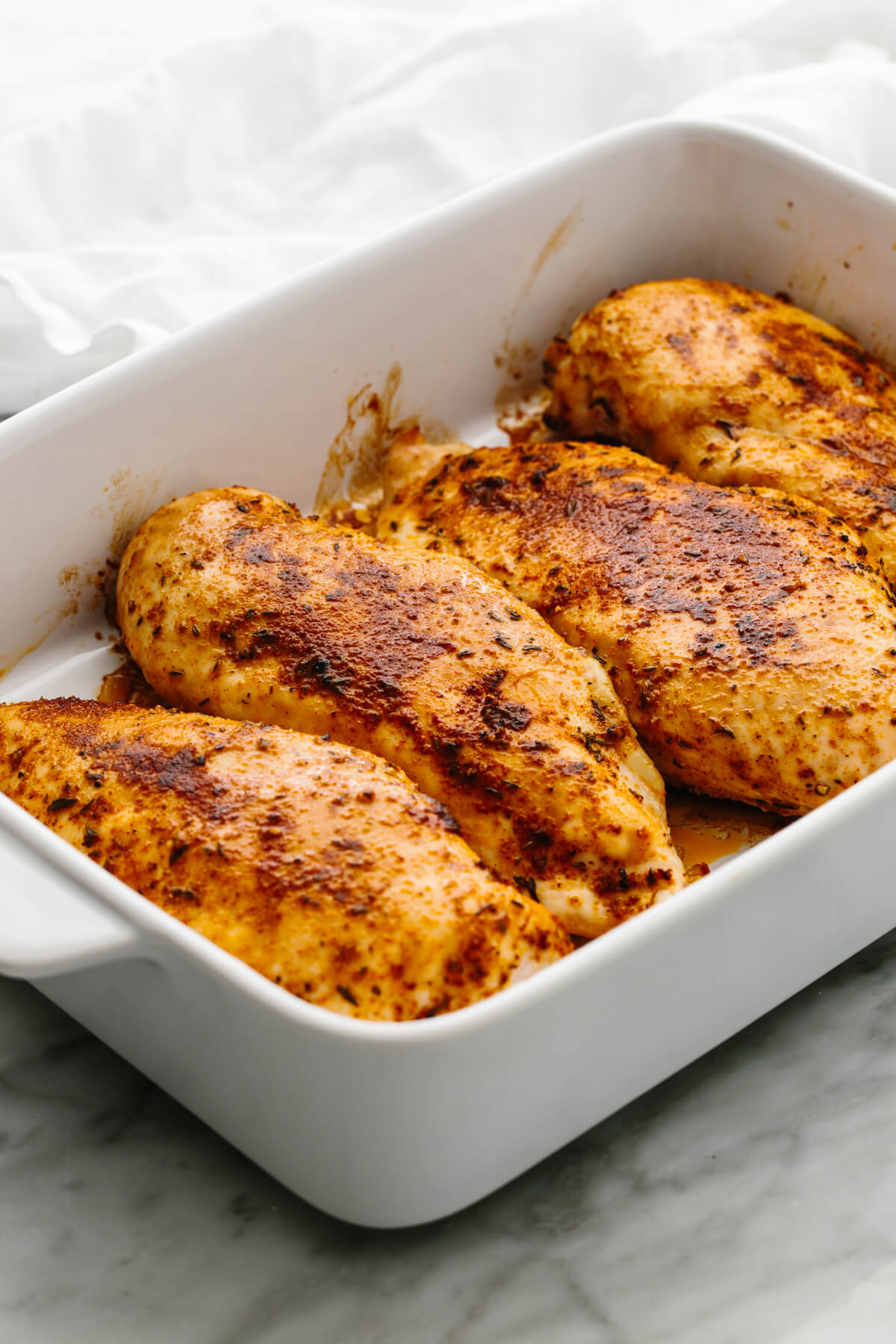 Four chicken breasts in a baking dish.