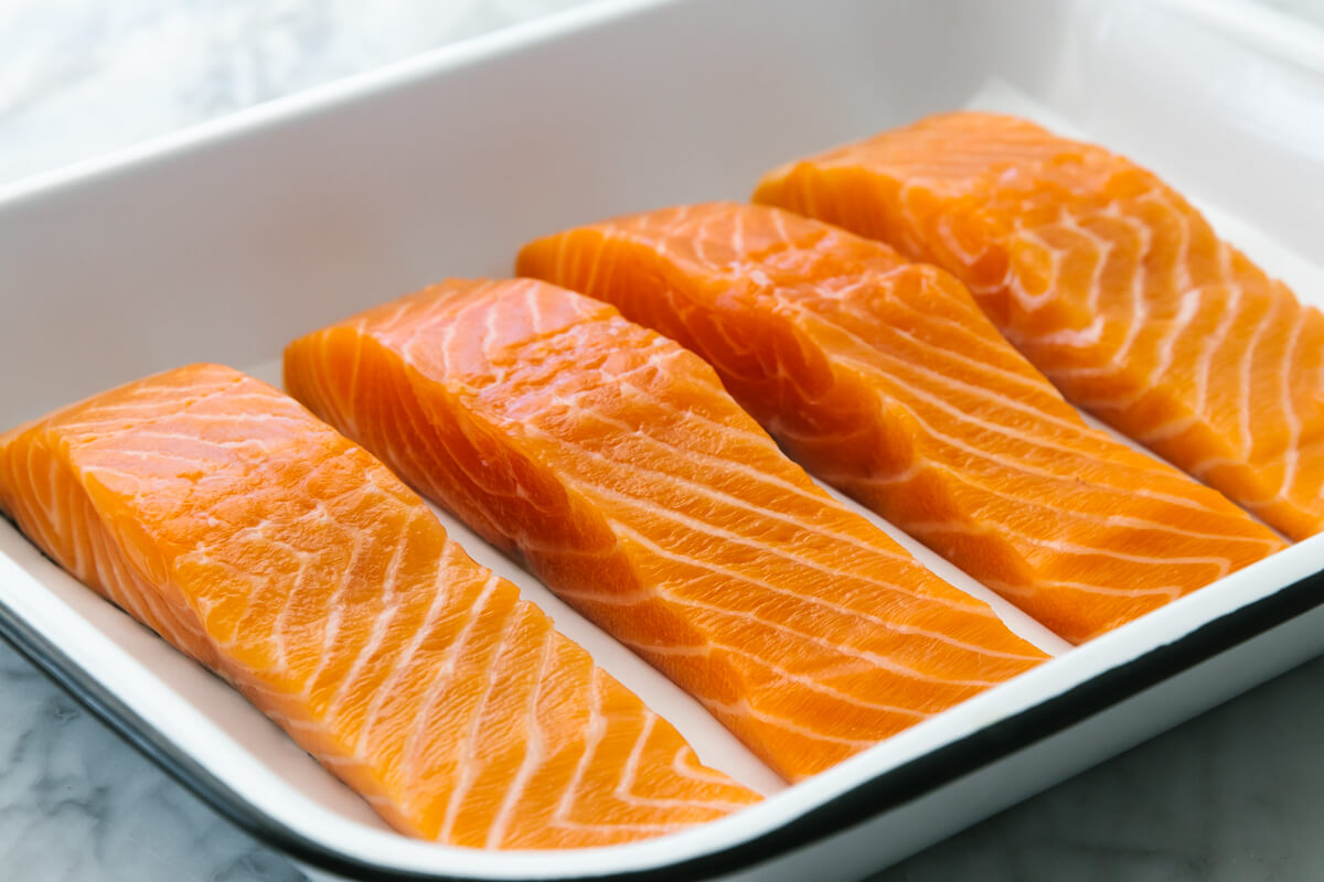 Raw salmon filets in a baking dish.