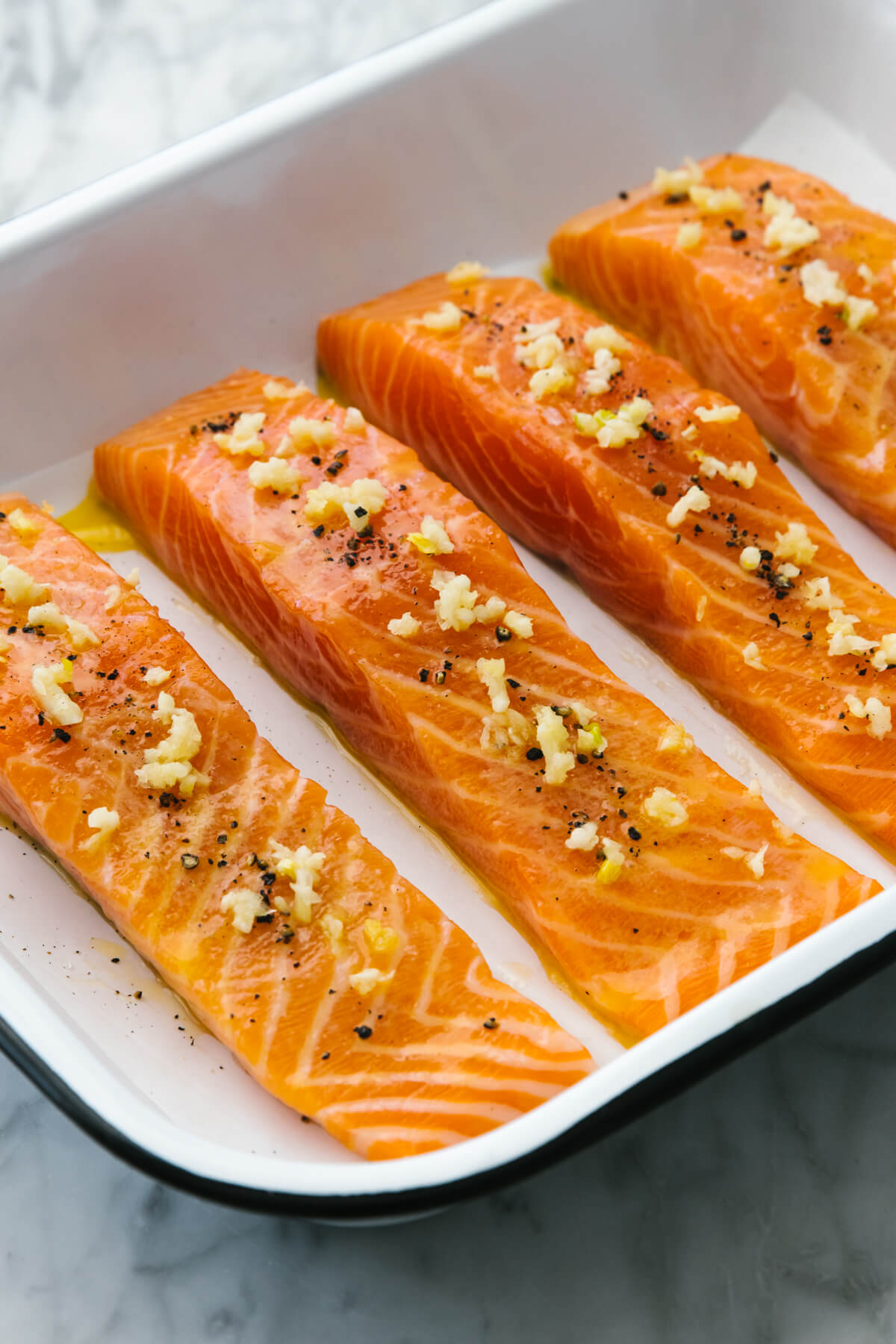 A pan with baked salmon and garlic butter sauce.