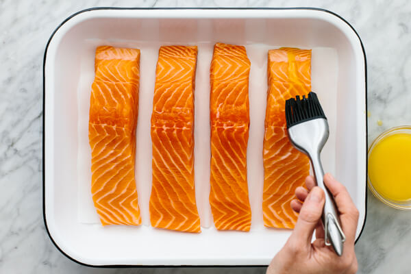 Baked salmon fillets with butter being brushed onto them.
