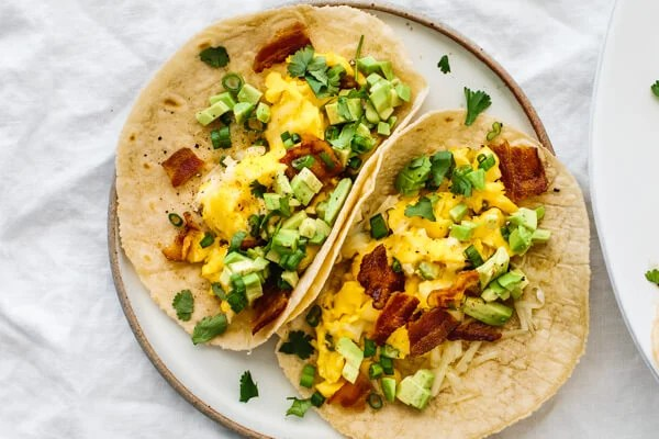 A plate with two breakfast tacos.