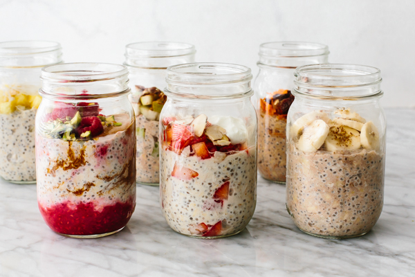 Different flavored overnight oats in jars on table.