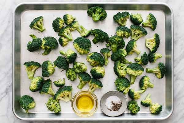Broccoli on a sheet pan to be roasted.