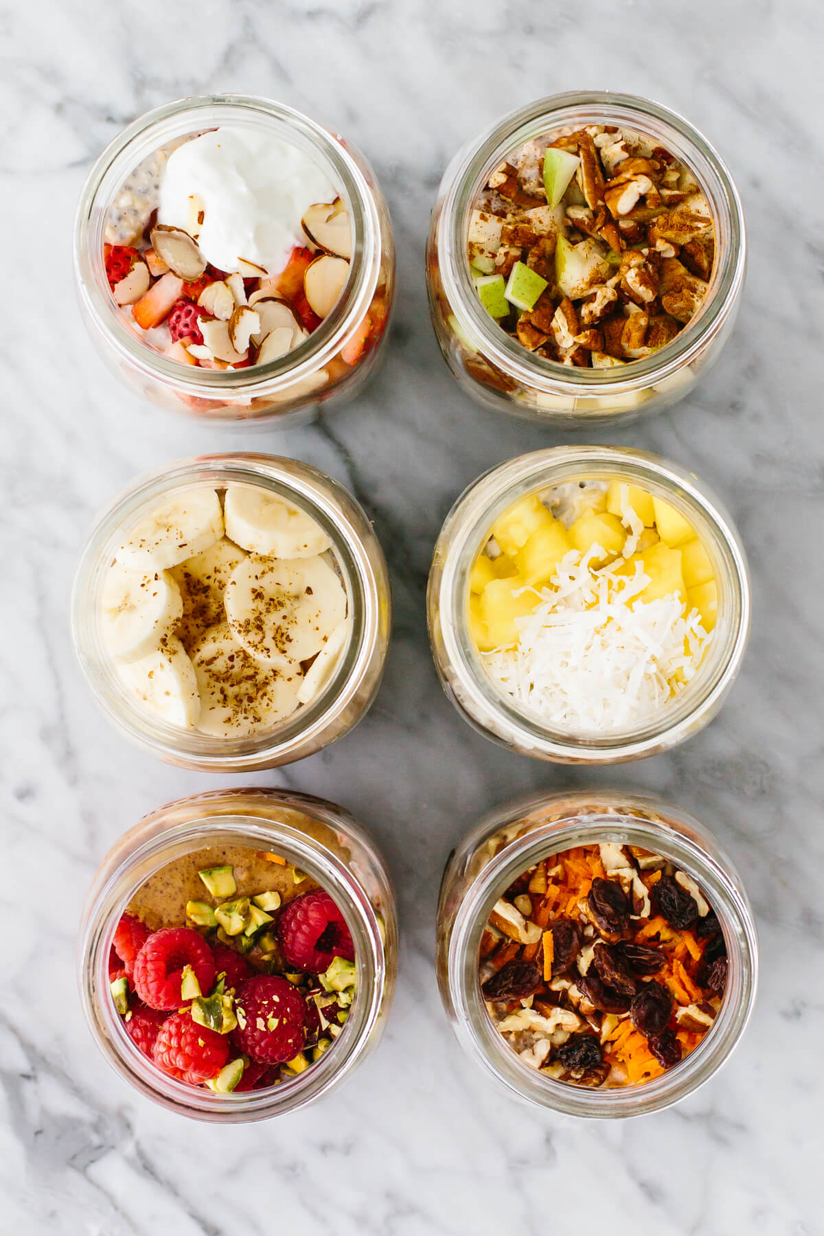 Overnight oats with different flavors in jars on a table.