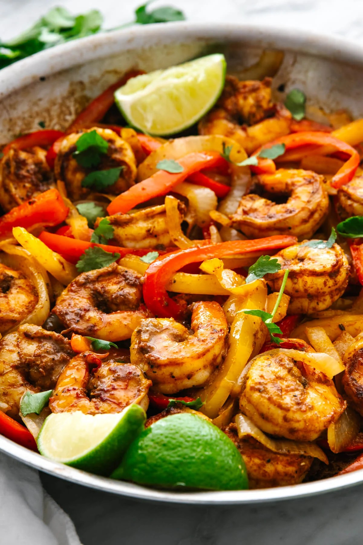 A pan of shrimp fajitas with limes.
