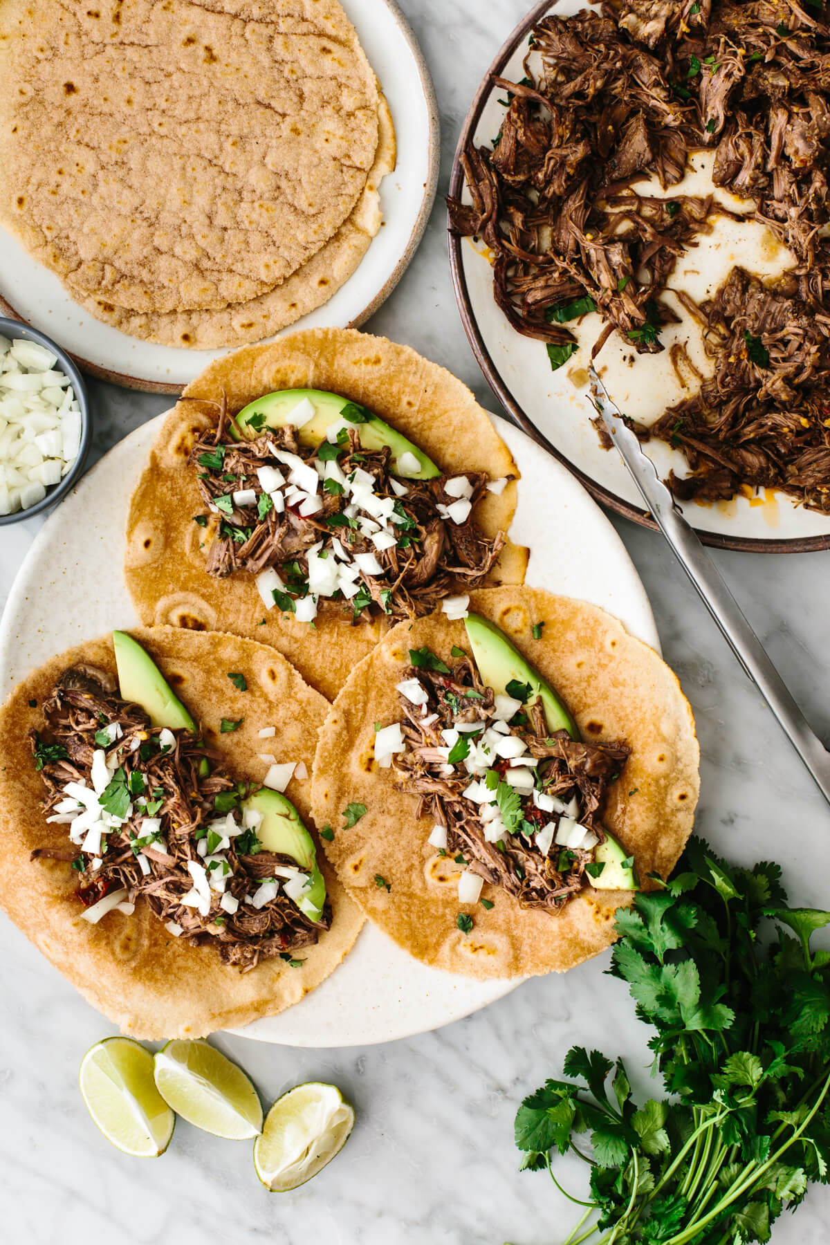 Assembling beef barbacoa tacos with tortillas.