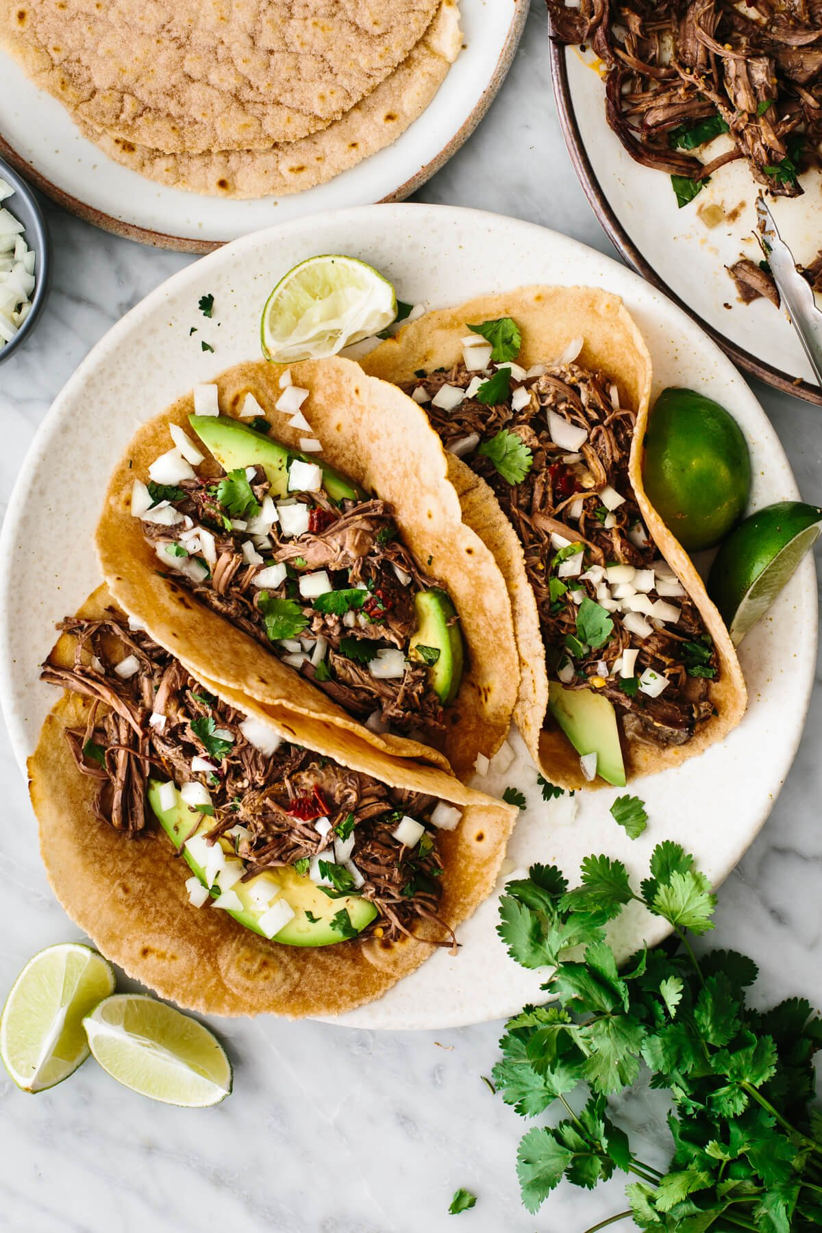 Barbacoa tacos on a plate with cilantro and lime wedges.