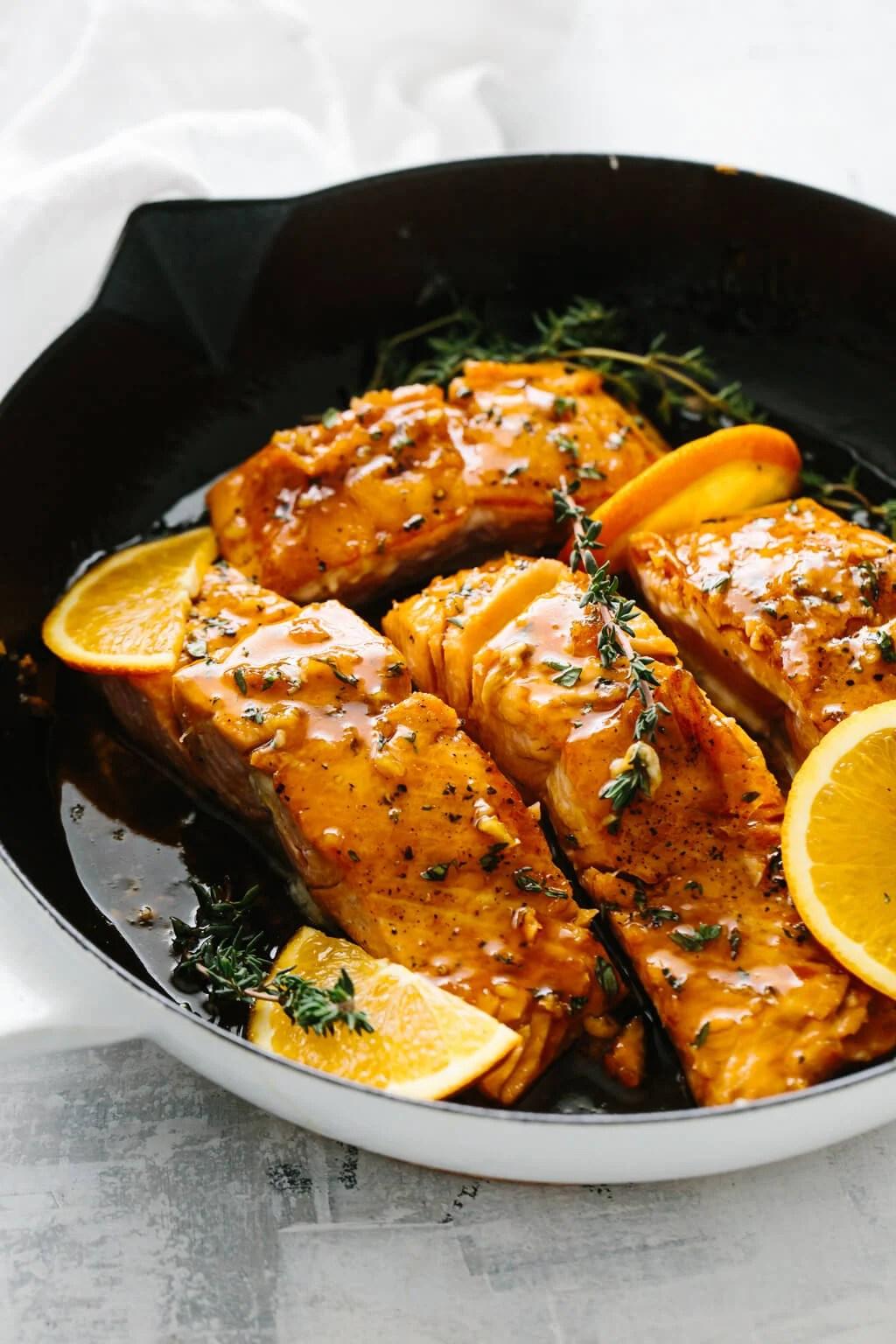 Orange glazed salmon in a pan.